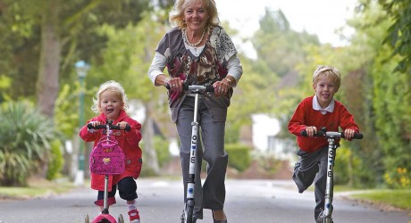 71 year old Grandmother Angela Nelson from Felpham, West Sussex, takes her two grandchildren on the school run on a scooters