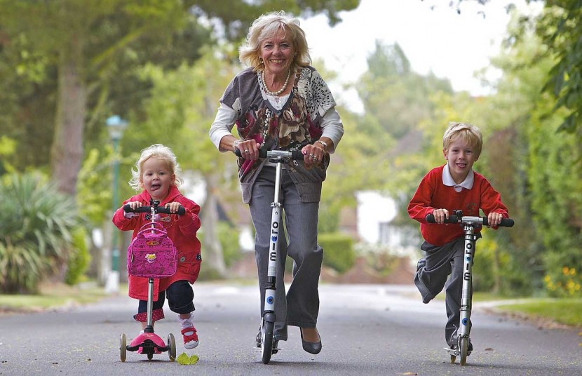 Granny takes kids to school on a scooter