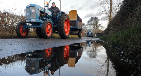 A Fordson tractor is reflected in a puddle as it takes part in the annual vintage tractor run to Haughton, Stafford.