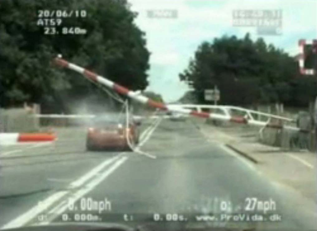 Car smashes through level crossing escaping police