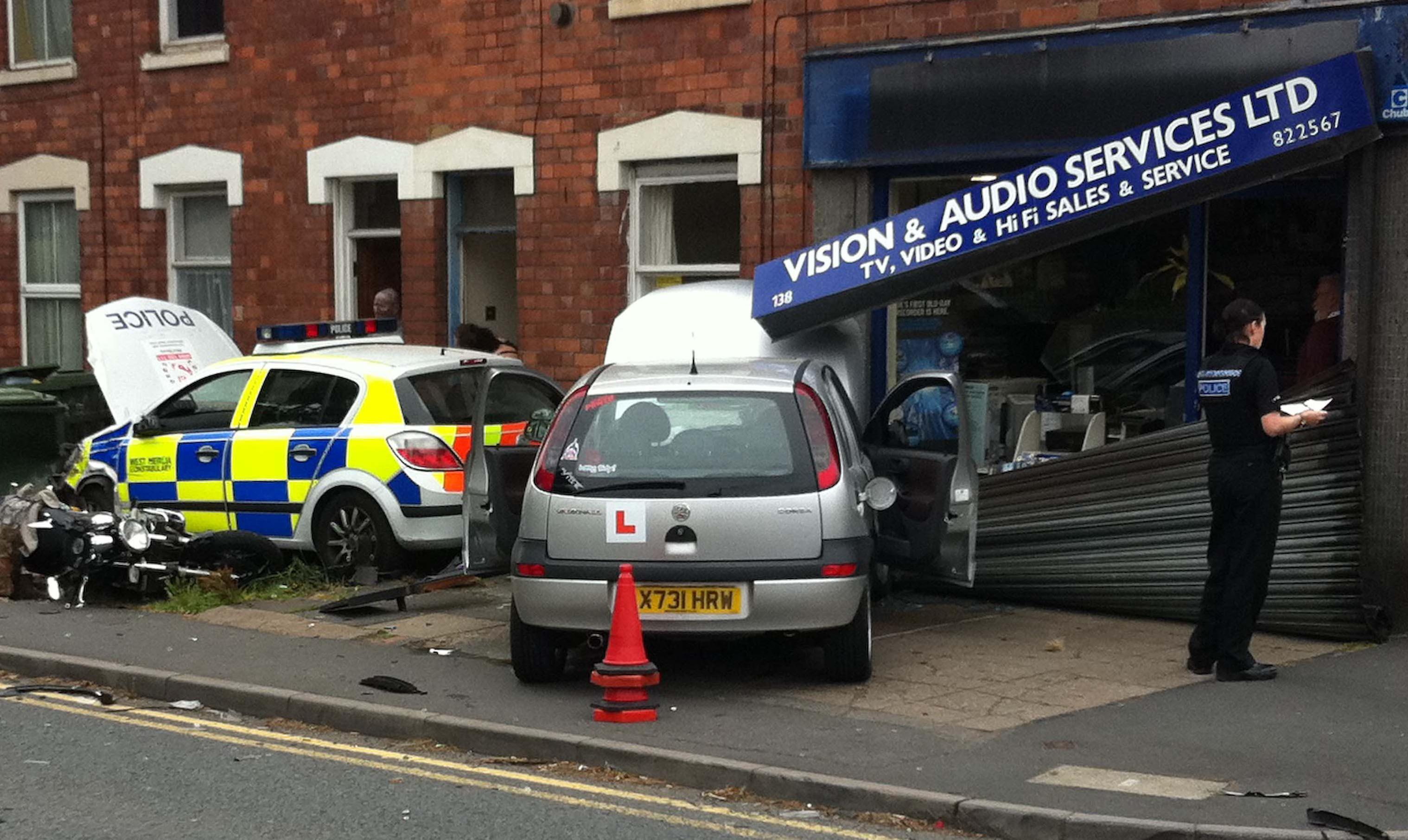 Police car crashes into shop front